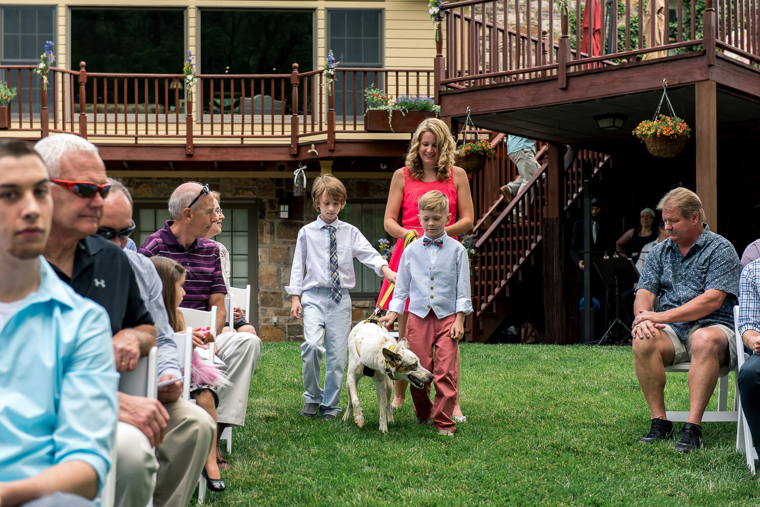 ring bearers walking dog down the aisle at backyard wedding