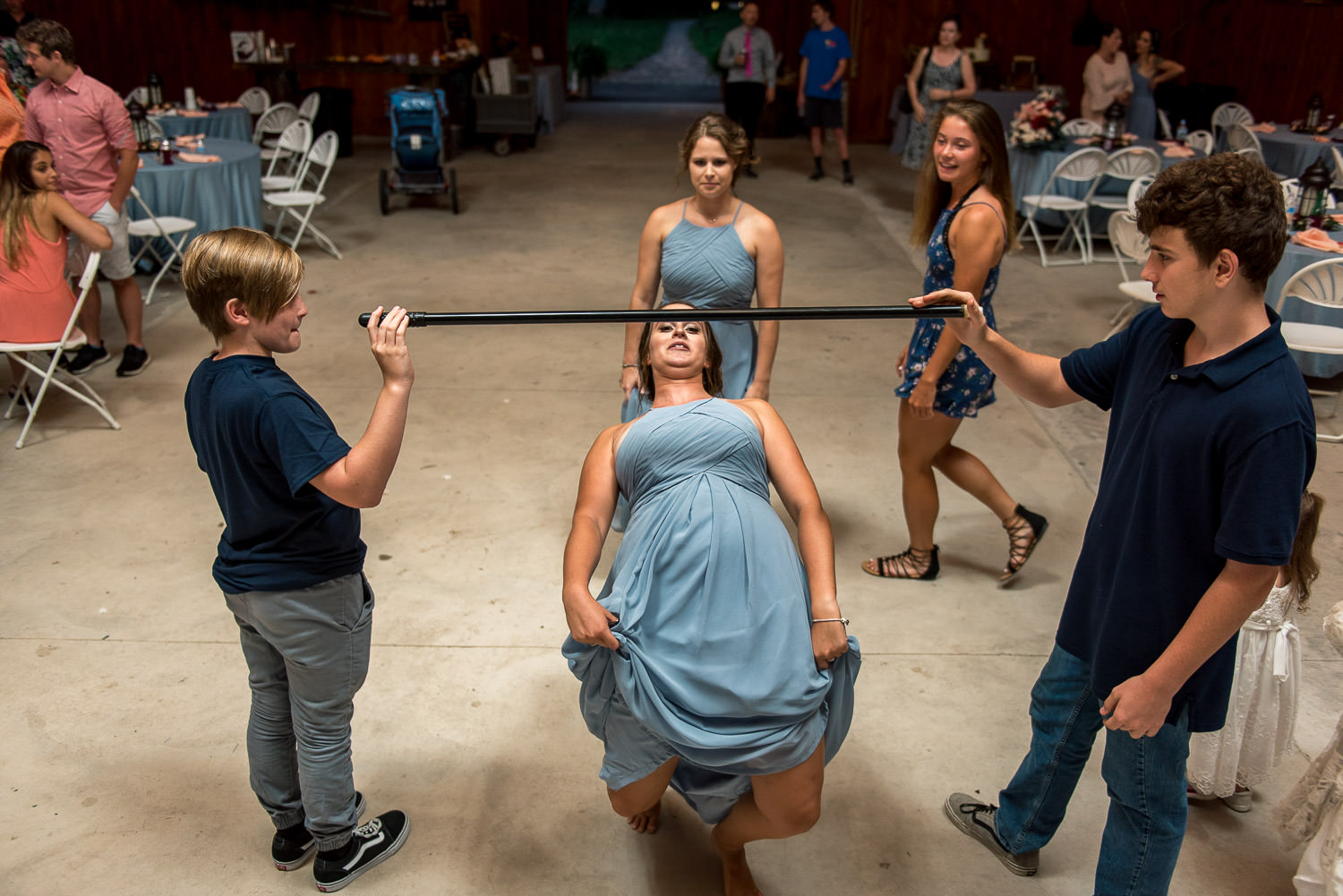 guests play limbo at wedding reception