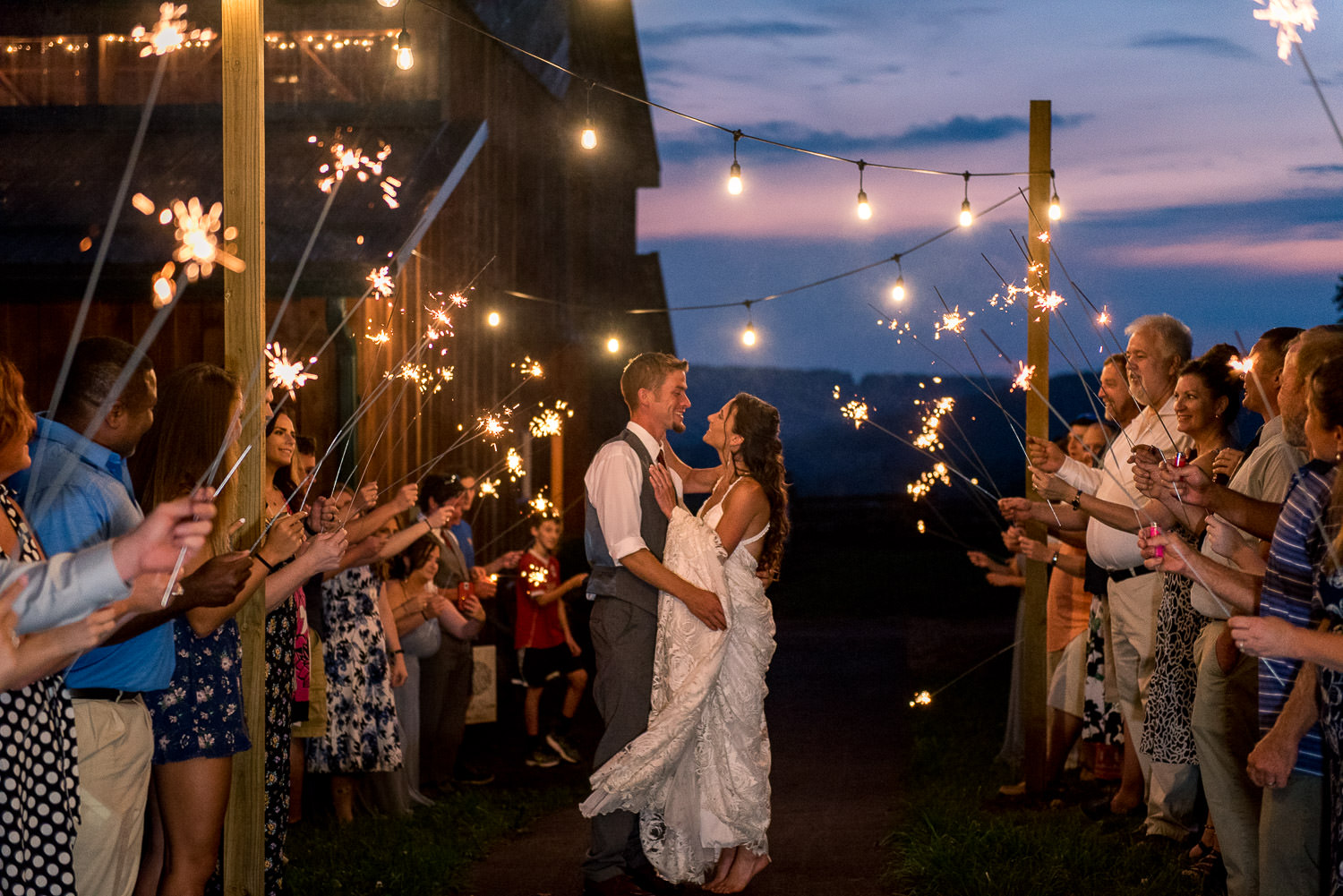 Bride and groom pose for portrait amid guests holding sparklers
