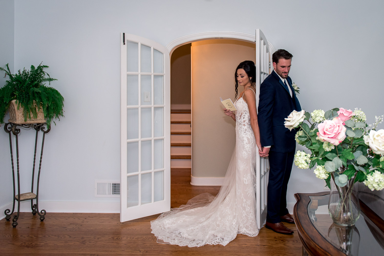 bride and groom holding hands with backs against a door as unique twist on a first look