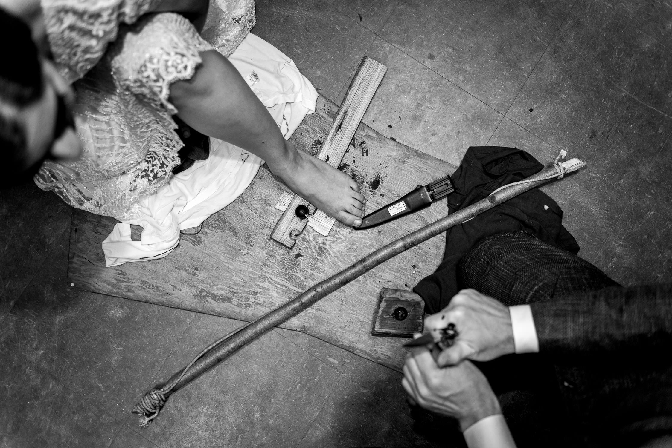Birds eye view of bride and groom building fire by rubbing sticks together