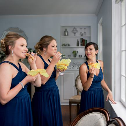 Candid photo of bridesmaids eating hamburgers