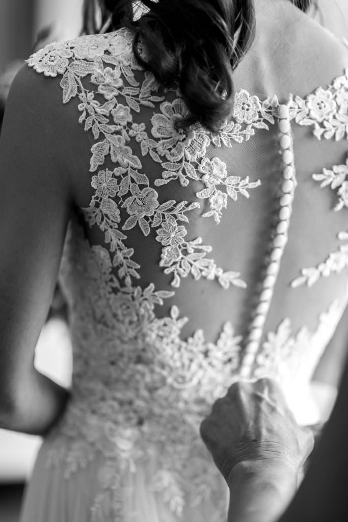 Detail photo of buttons and lace on bride's boho dress