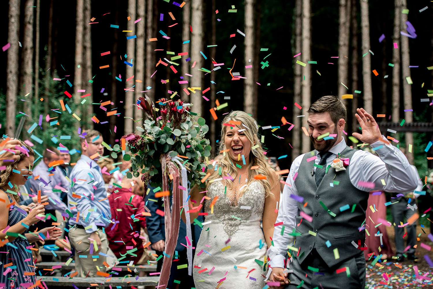 wedding guests throwing confetti as bride and groom exit wooded outdoor ceremony site