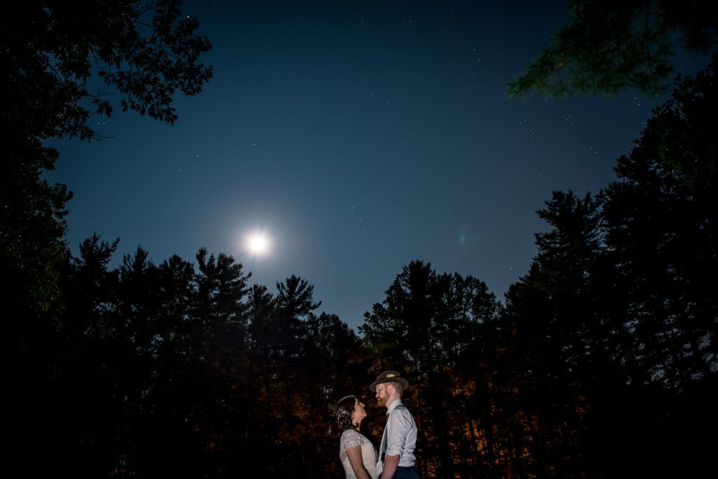 Night portrait of bride and groom in woods under the moon and stars