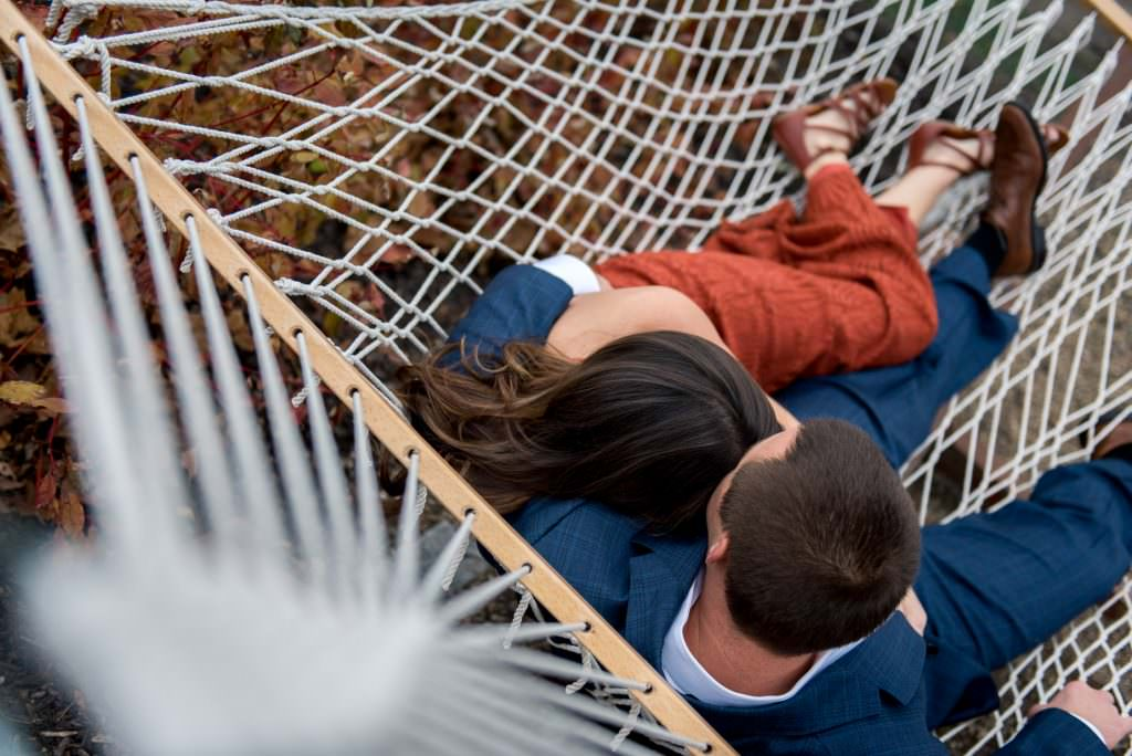 Creative portrait of engaged couple cuddling in hammock at Omni Bedford Springs