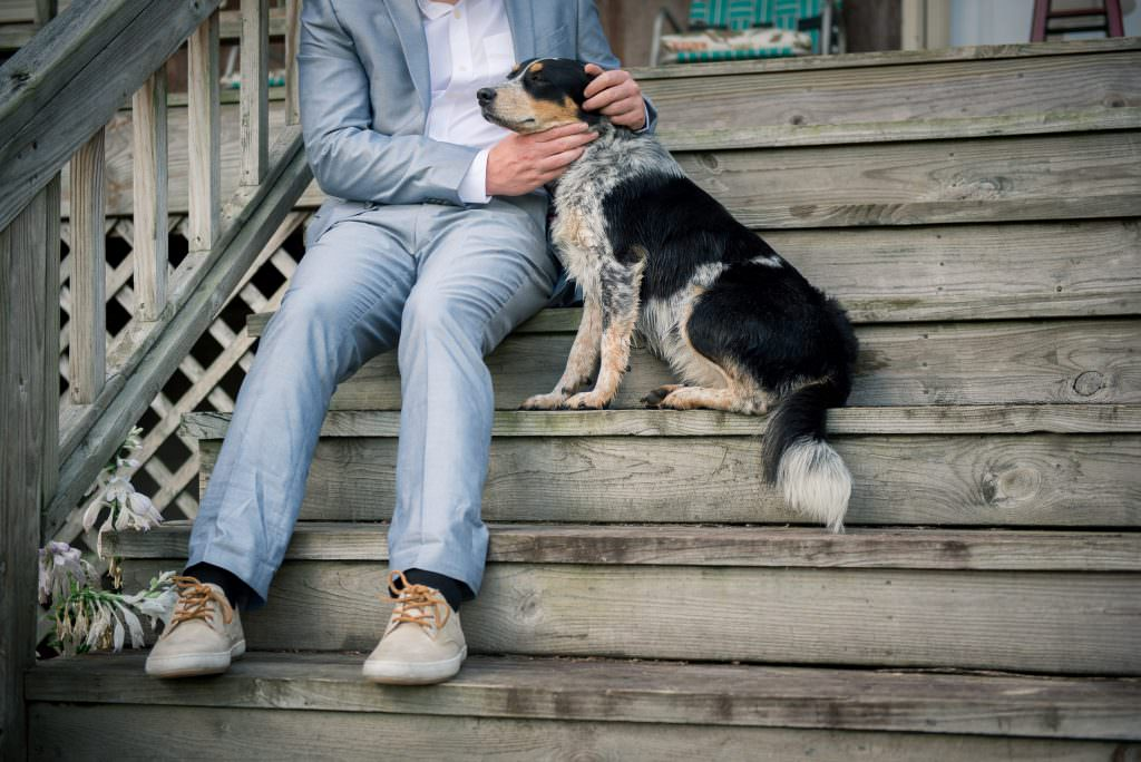 Candid photo of groom petting blue heeler dog on porch
