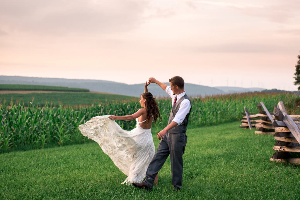 Groom twirling bride at sunset in field