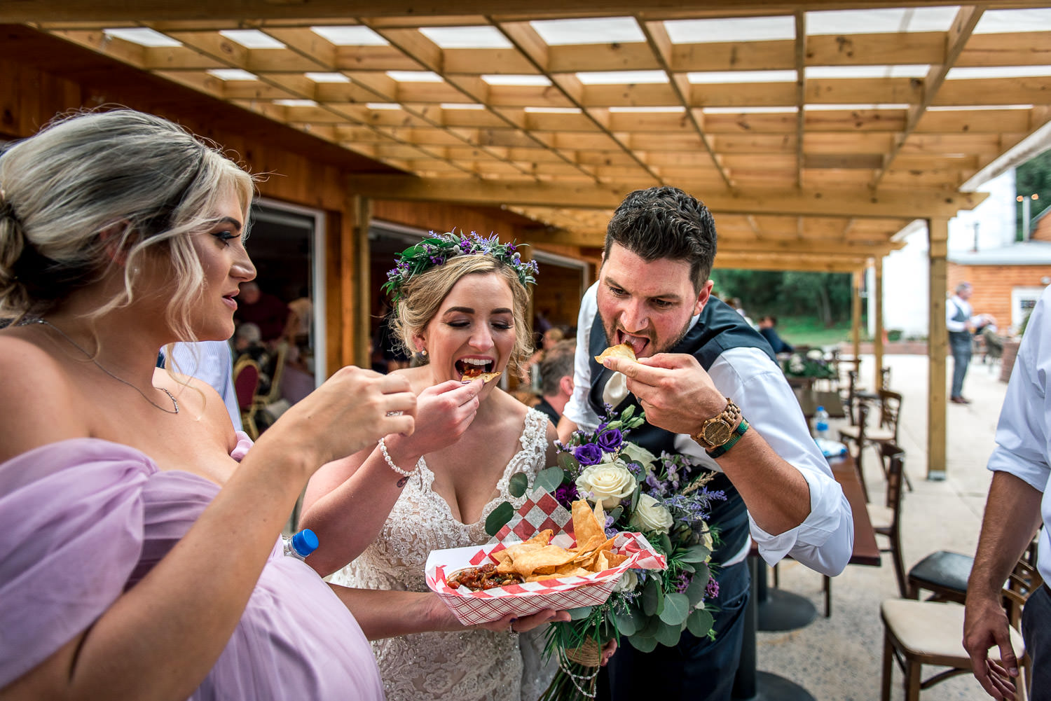 Bride and groom eat nachos for the food truck at their wedding reception