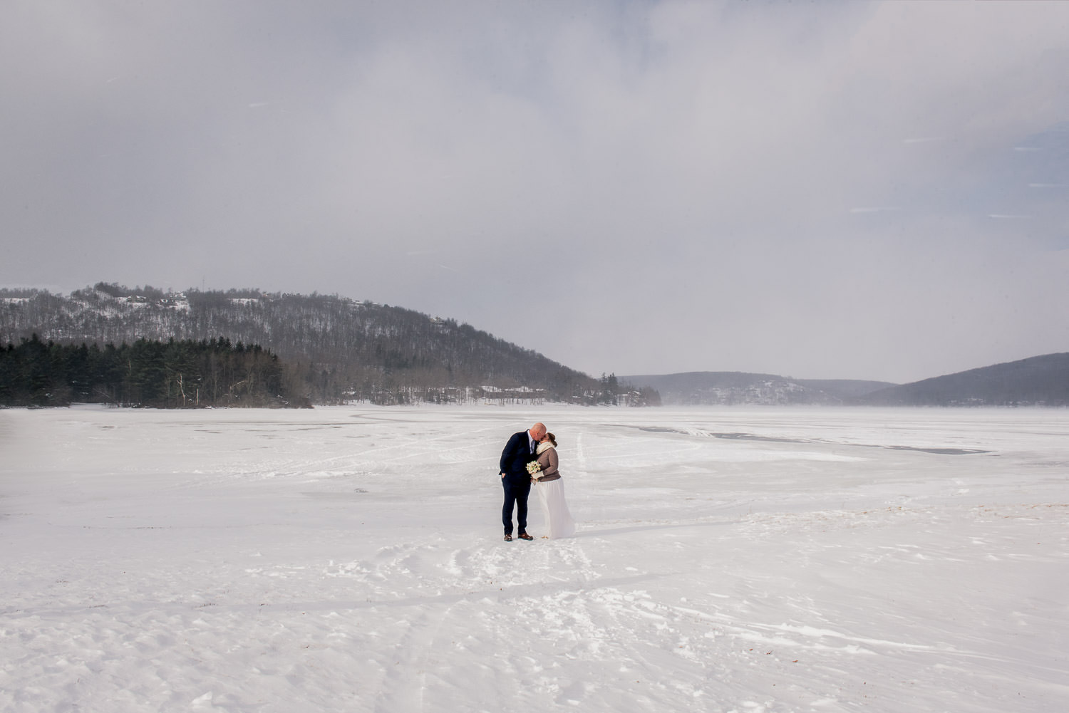 bride and groom on a frozen lake