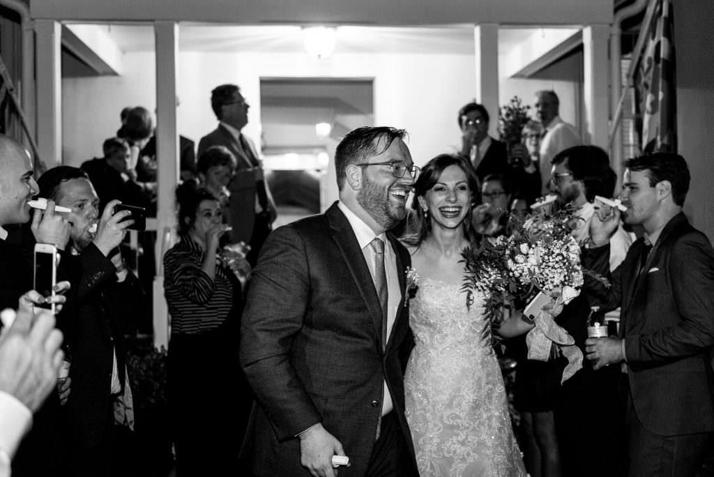 candid wedding photo of bride and groom exiting reception at night