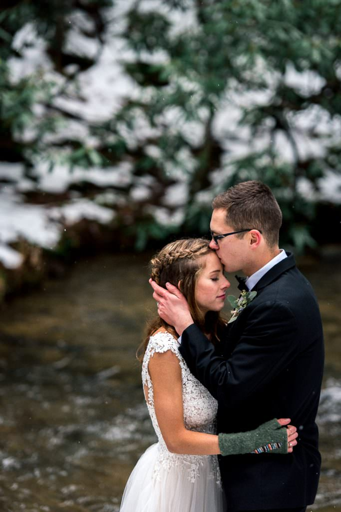 Winter elopement groom kissing bride in snowy woods