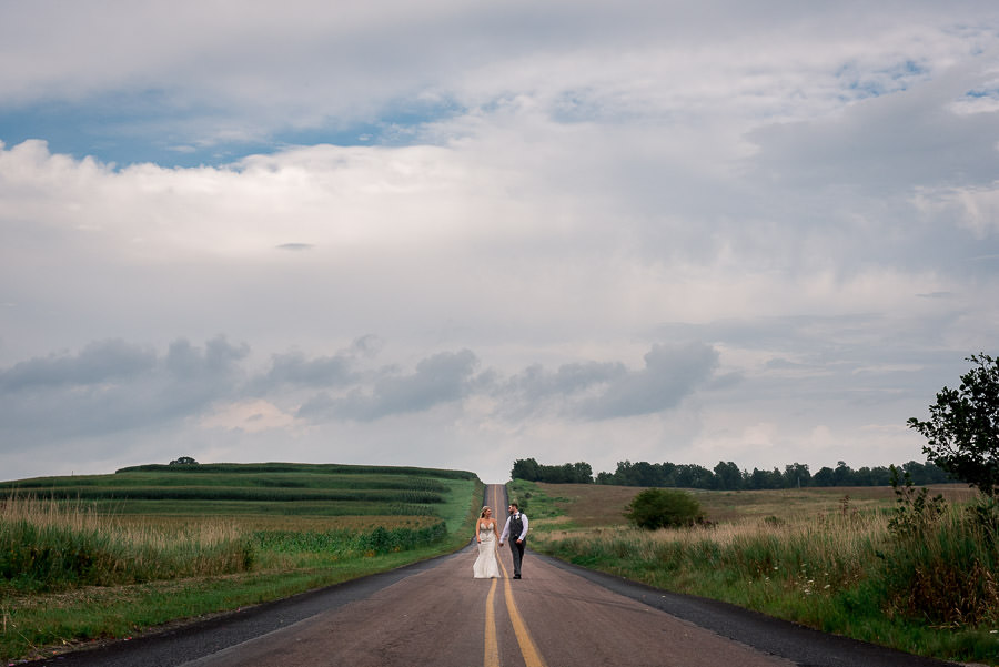 bride and groom walking down open road under big cloudy sky in Allegheny Highlands Pennsylvania