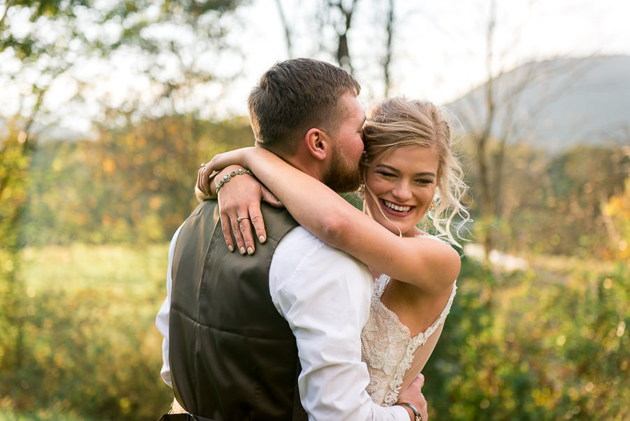 groom kissing brides forehead during golden hour portraits