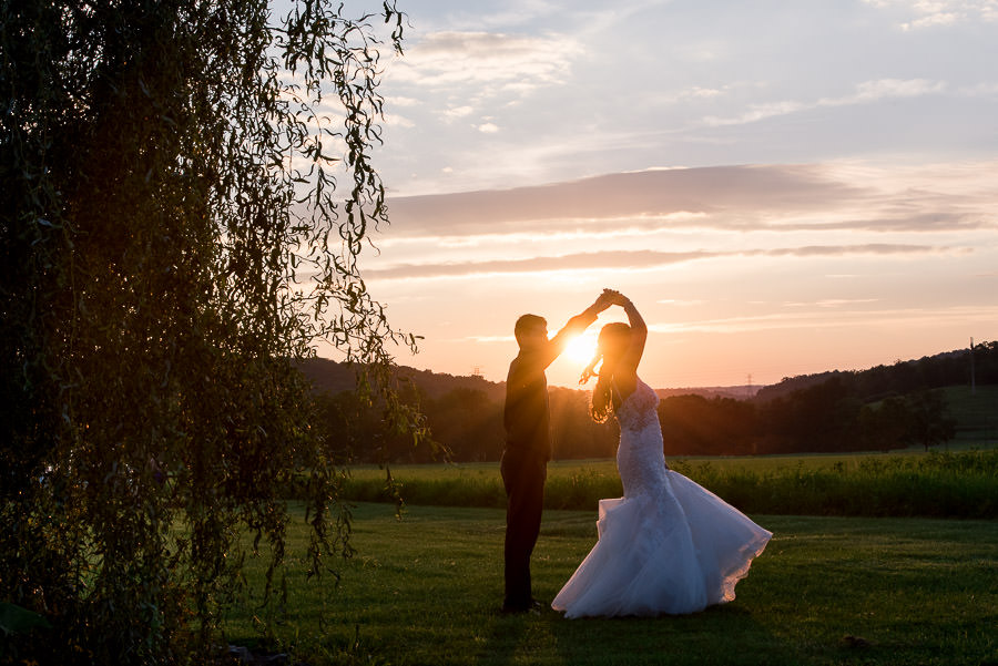 silhouette of groom twirling bride at sunset by willow tree