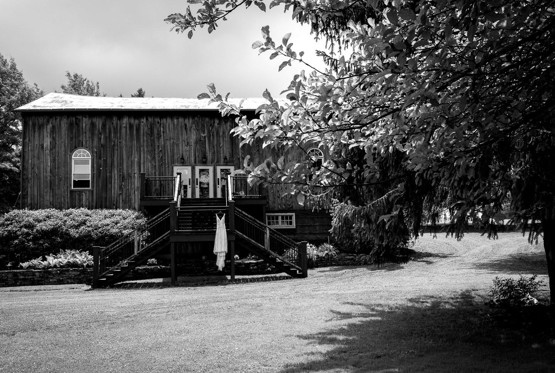 wedding dress hanging outside barn
