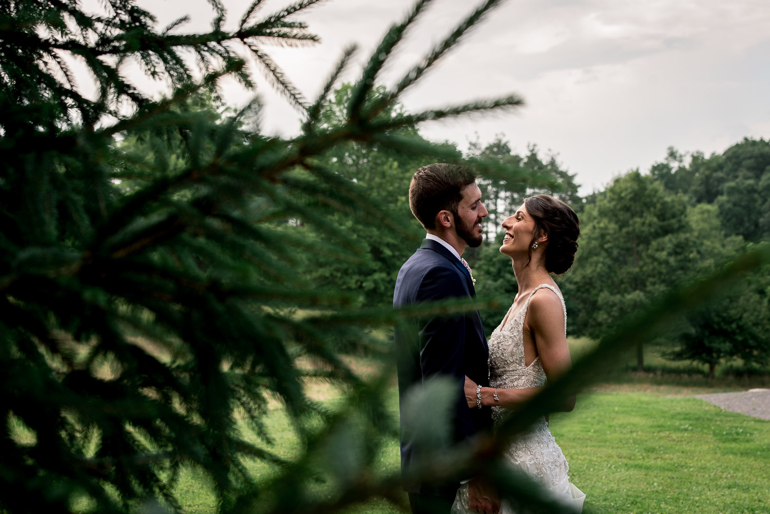 bride and groom by pine trees