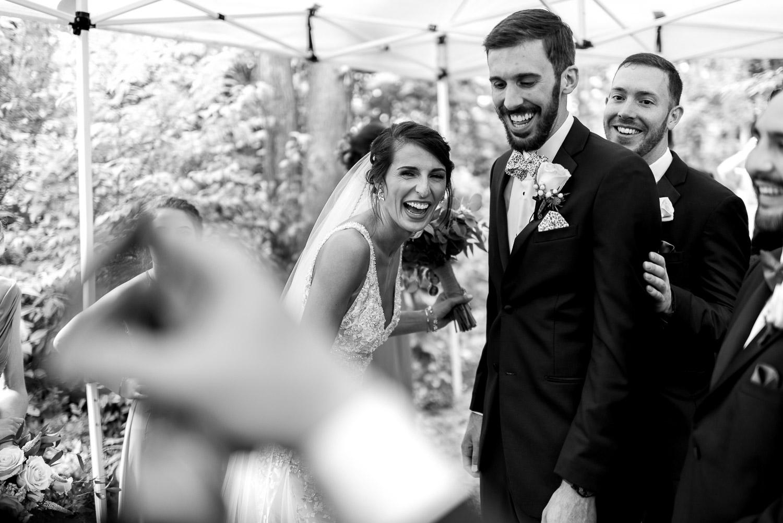 bride surprised by groomsmen under tent