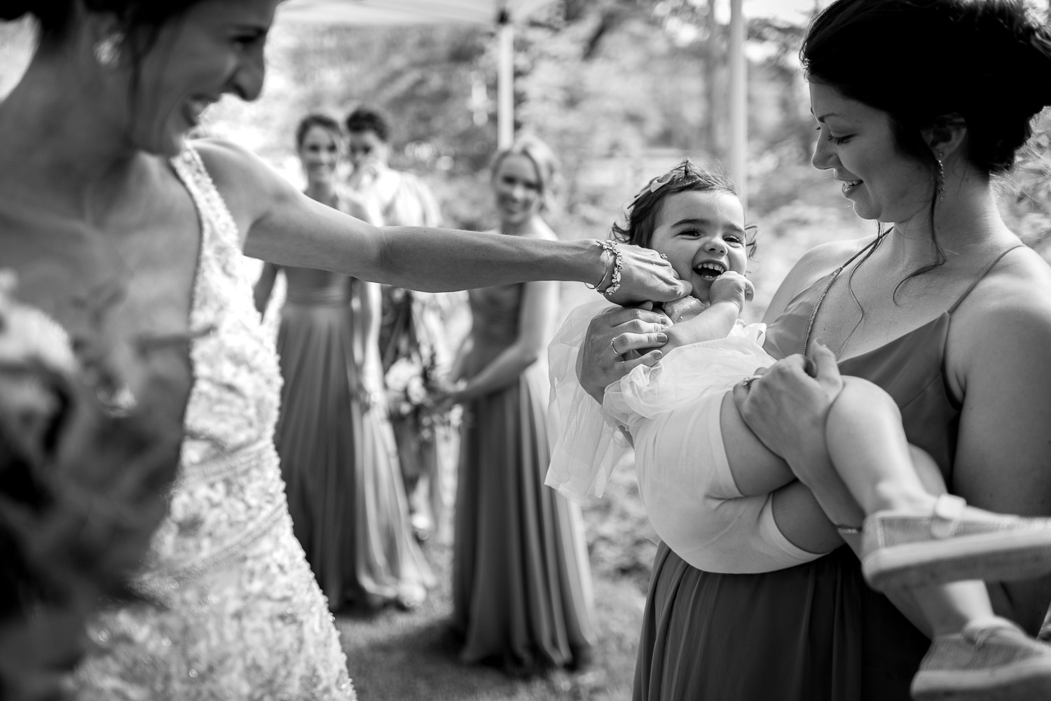 bride laughing with flower girl under tent