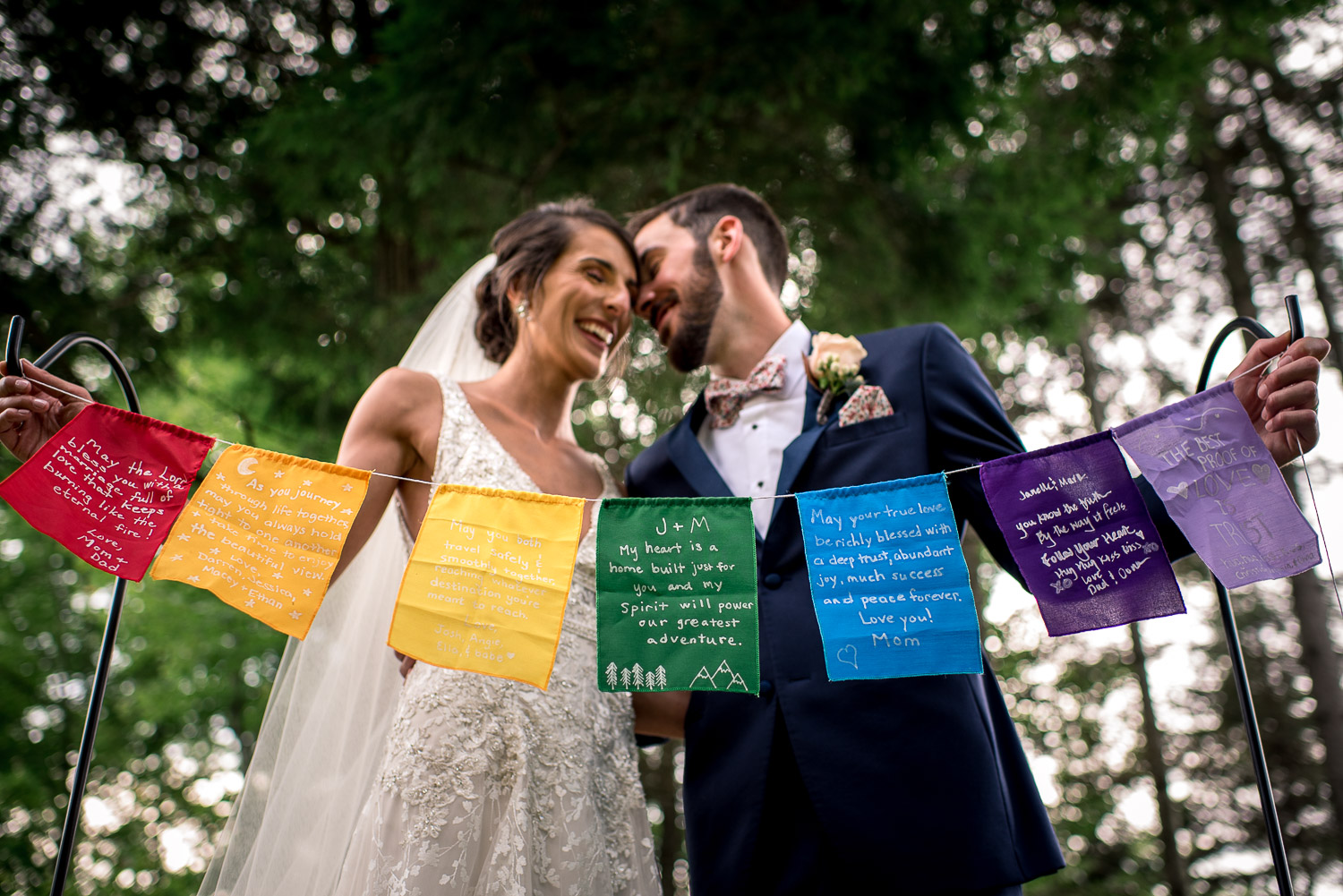 bride and groom posing with prayer flags in the forest