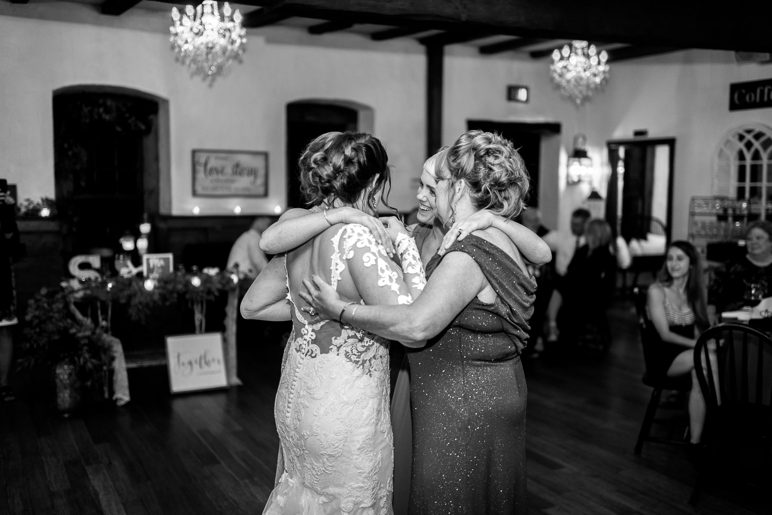 bride dancing with mother and sisters at wedding reception