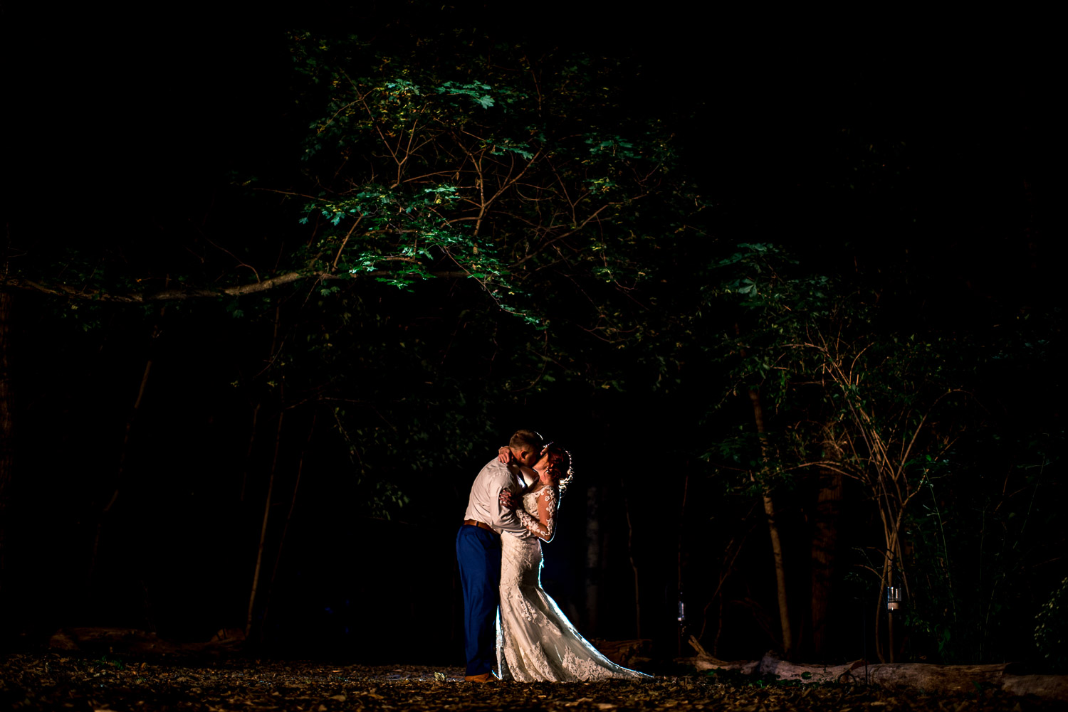 creative night portrait of bride and groom kissing in the forest