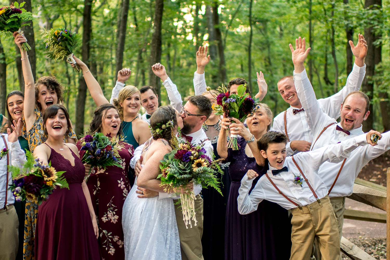 portrait of wedding party surrounding bride and groom in woods