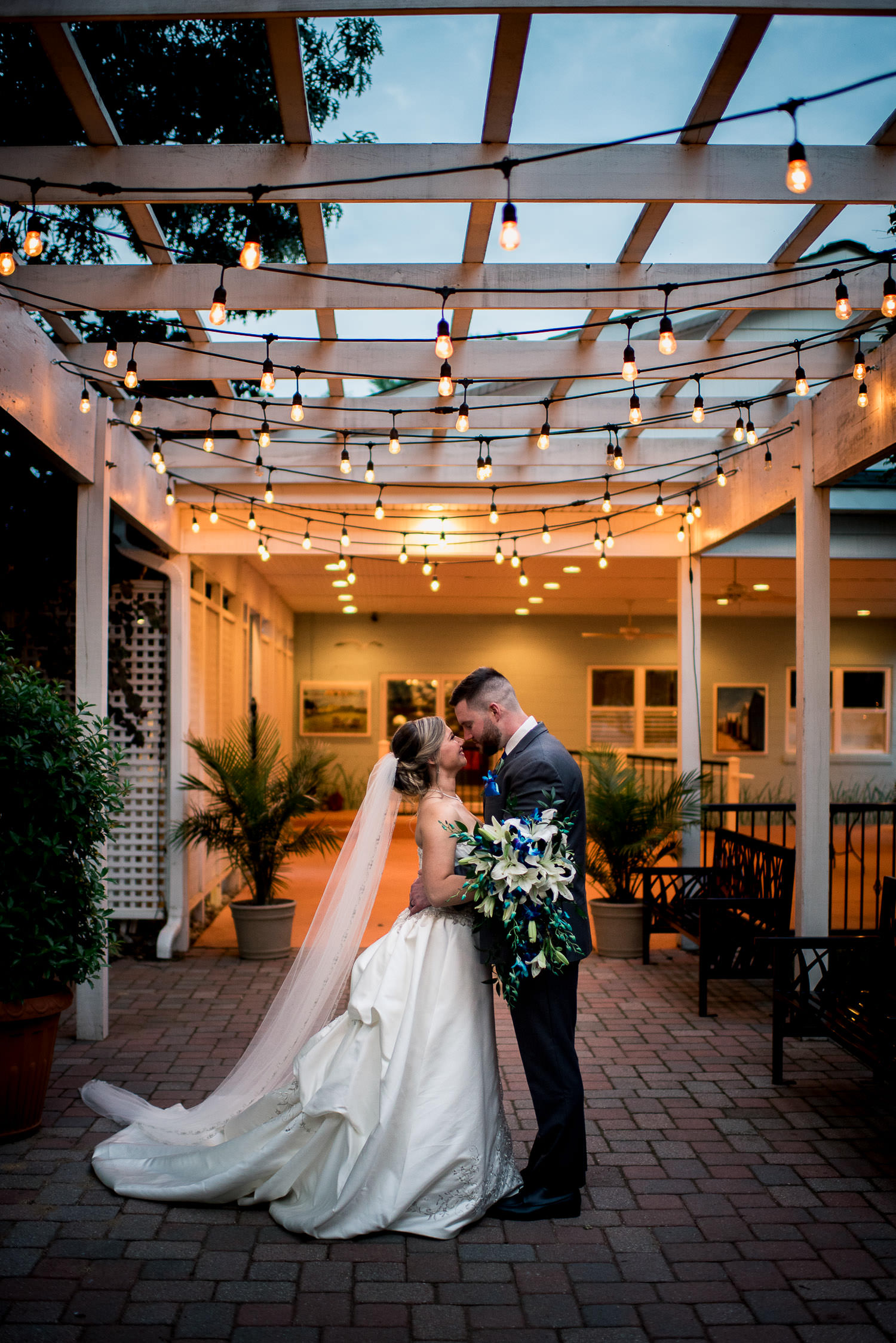 portrait of bride and groom under twinkle lights