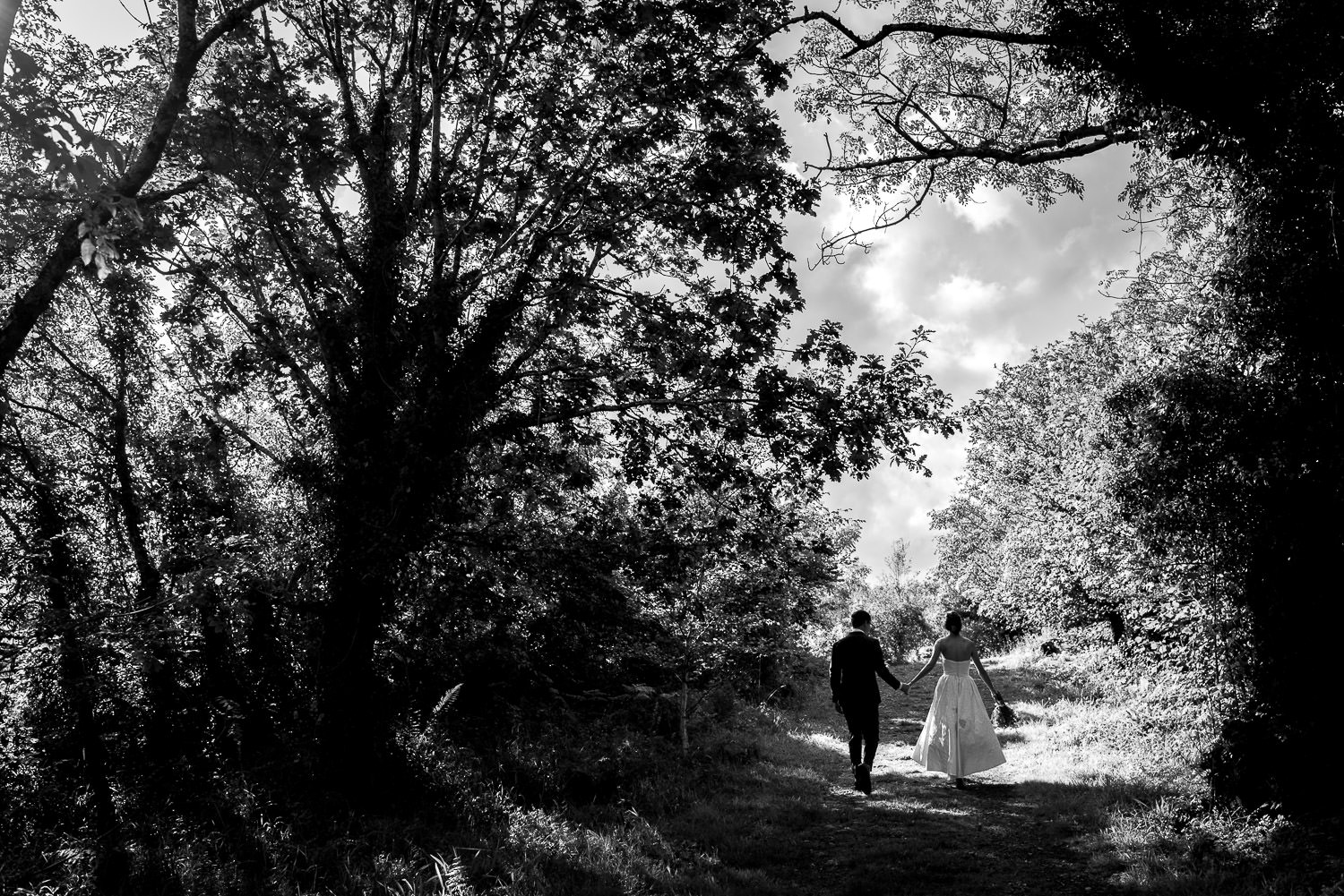 wedding portrait of bride and groom walking in the woods in Ireland