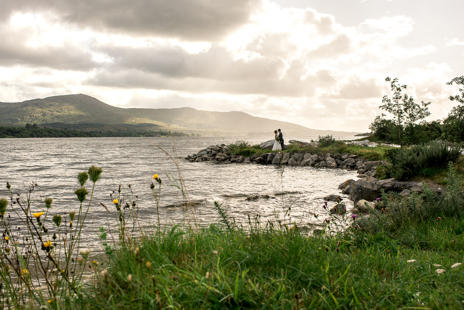 wedding with bride and groom standing on the edge of the Kenmare Bay in Ireland