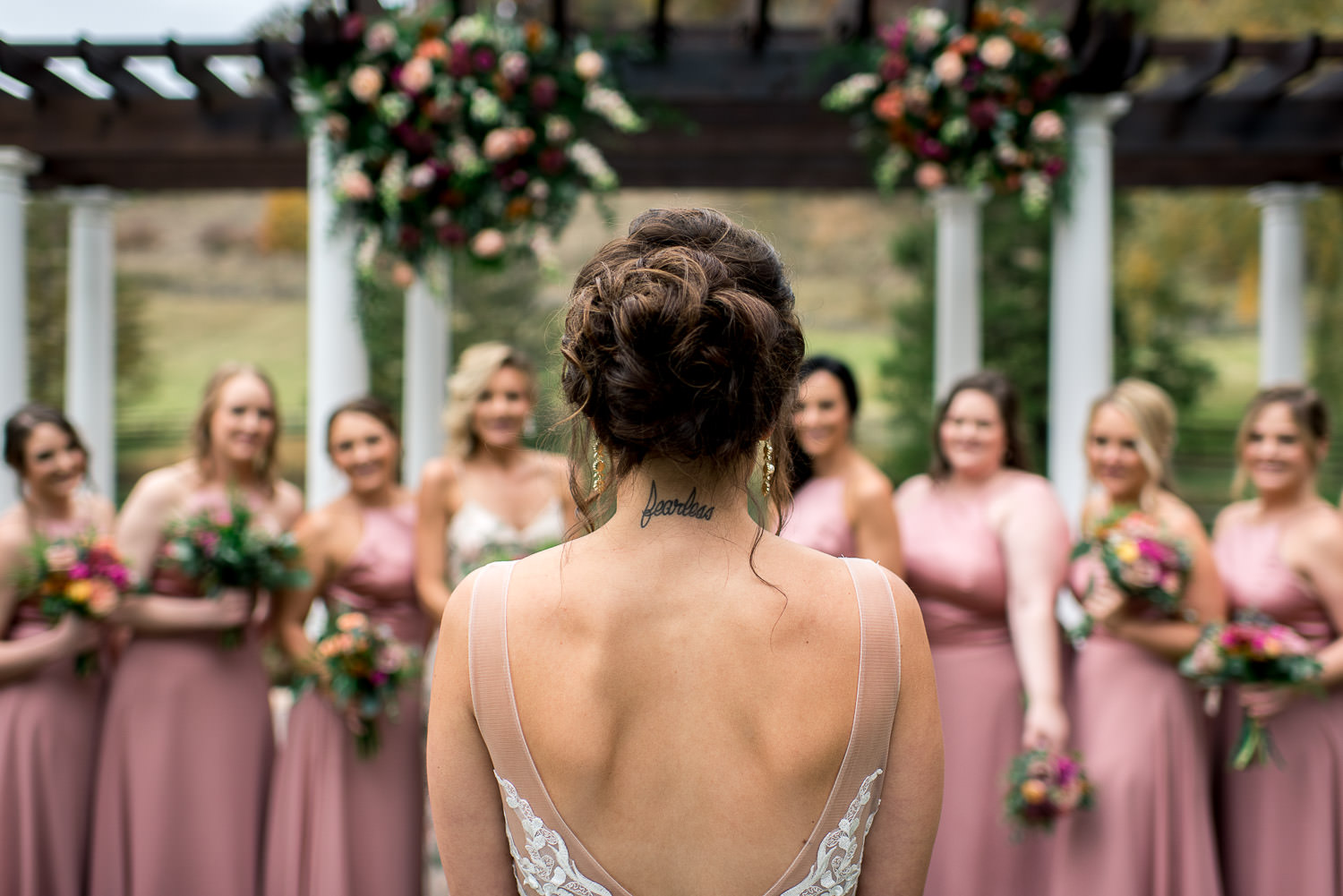 bride looking at her bridesmaids with fearless tattoo on neck