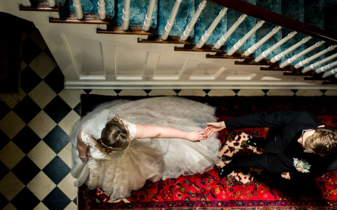 birds eye view of bride and groom reaching for each other in stairwell