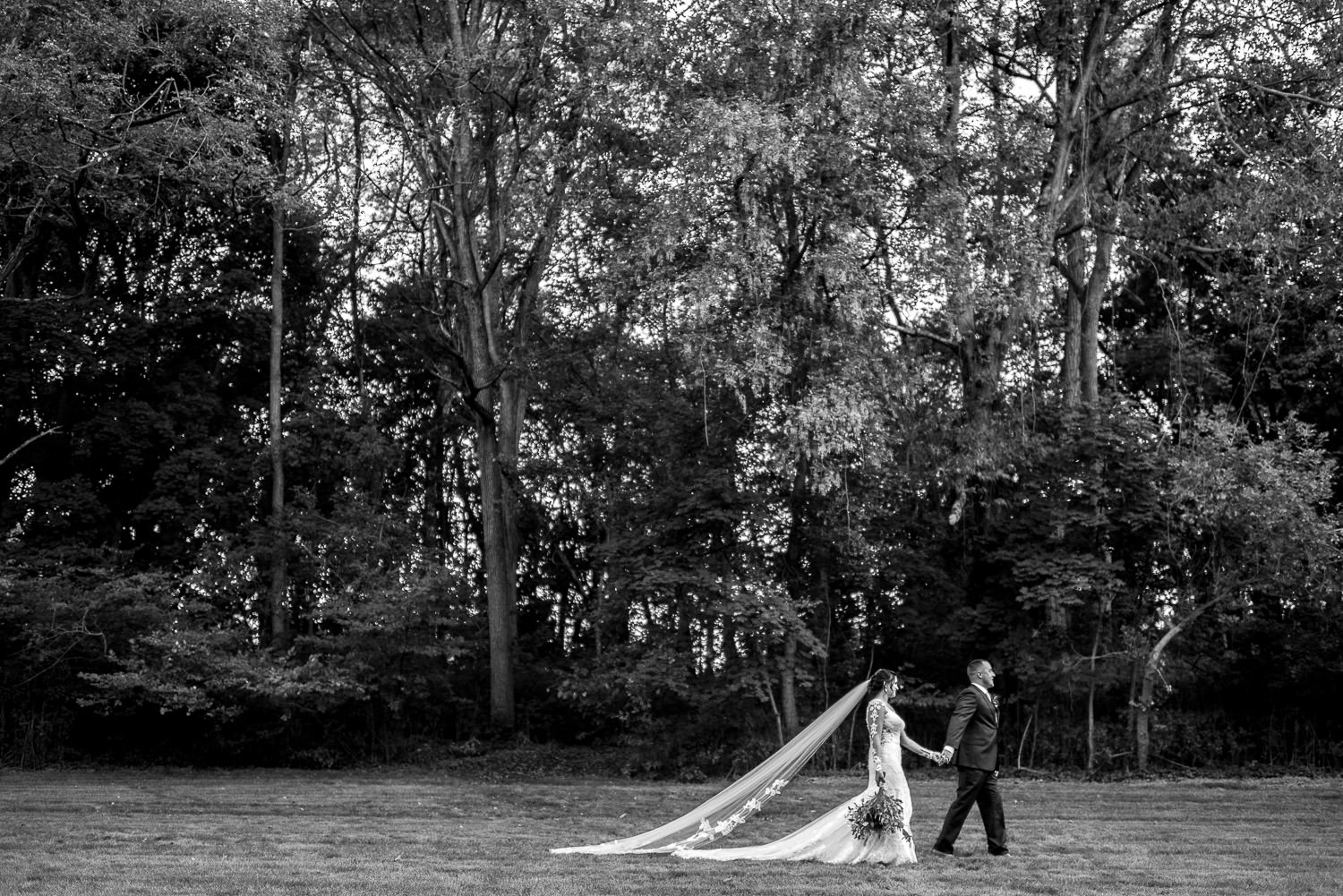 black and white portrait of bride and groom walking in field in York Pennsylvania