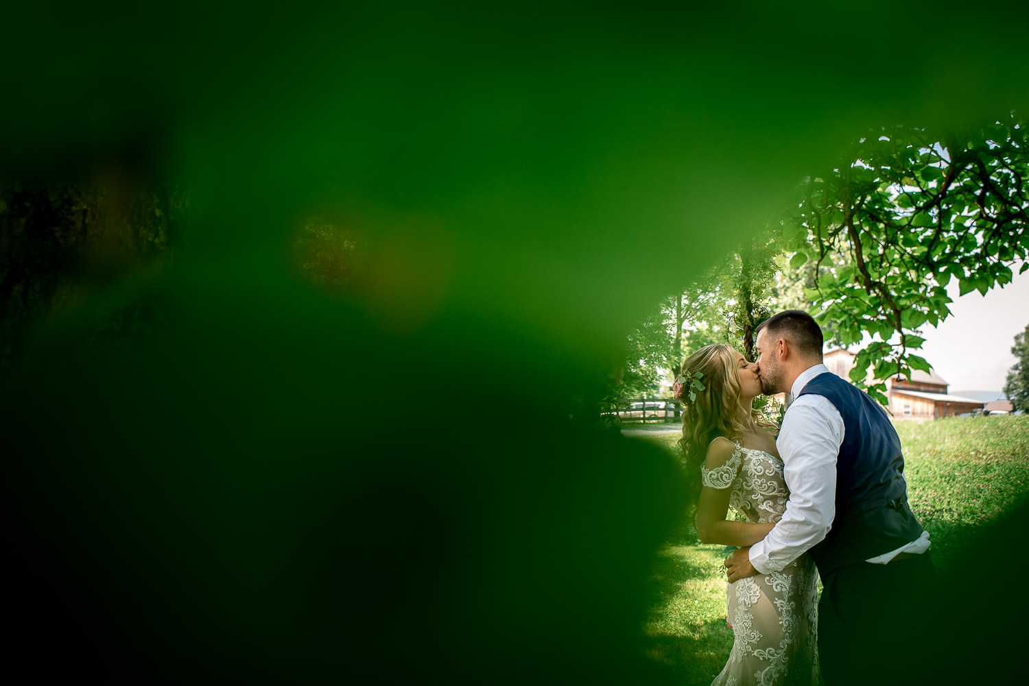 wedding portrait of bride and groom kissing under a tree