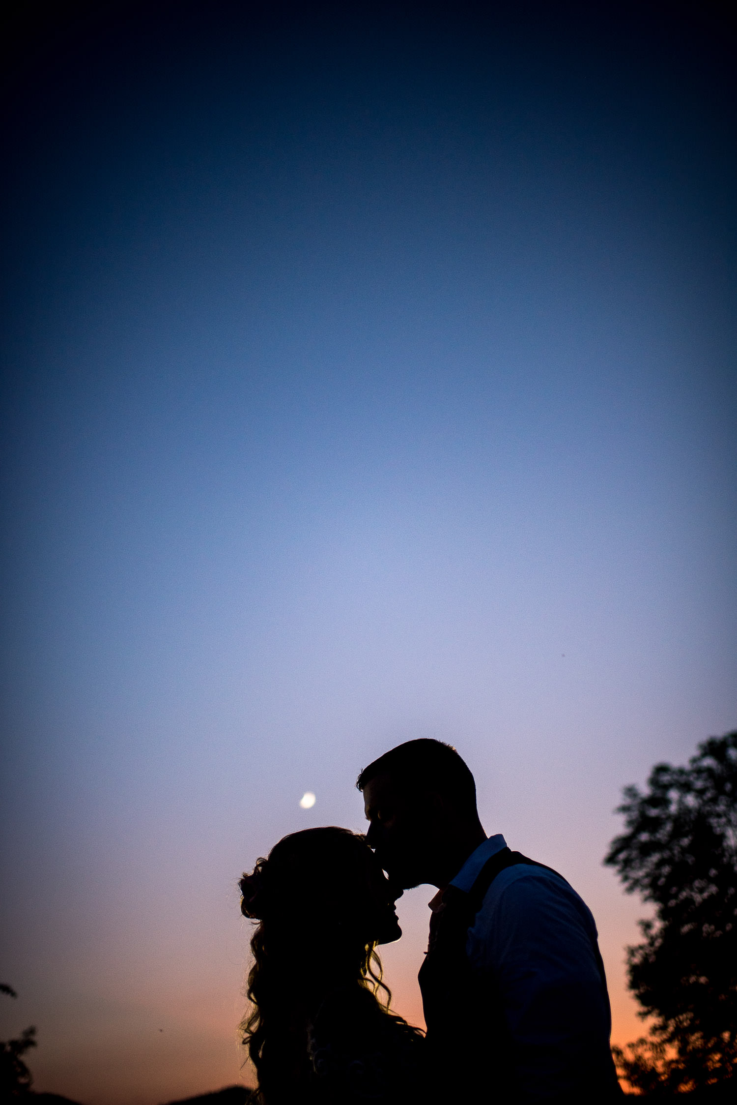 night portrait of bride and groom with moon in sky