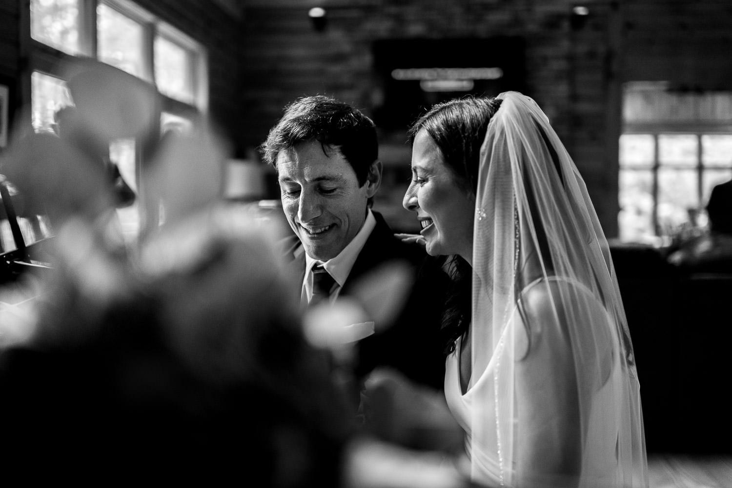 black and white candid wedding moment at piano