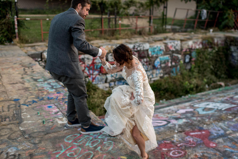 groom helps bride up graffiti wall