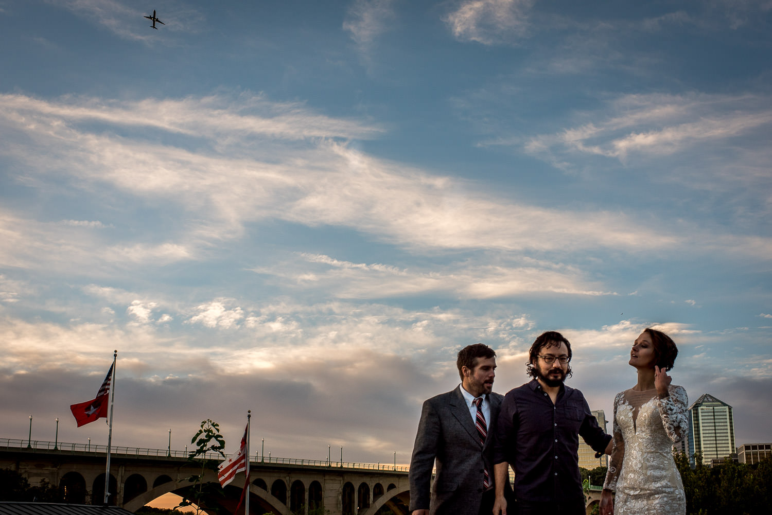 airplane flies over bride and groom